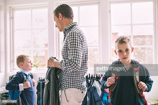 Father assisting sons in getting ready for school at home