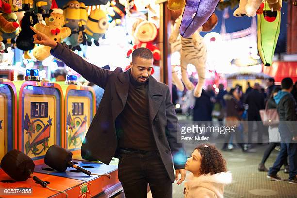 Father at amusement park selecting prize for daughter