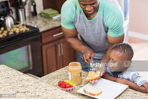 Father at home making peanut butter sandwich for son