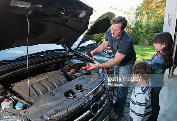 Father attaching jumper cables to car