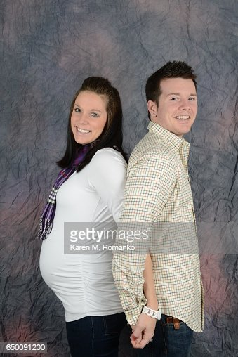 Father back to back with pregnant mother (8 months pregnant) smiling & holding hands : Stock-Foto