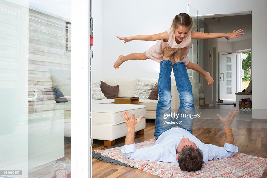 Father balancing his daughter on his feet : Photo