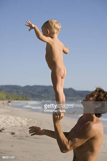 Father balancing naked son on beach