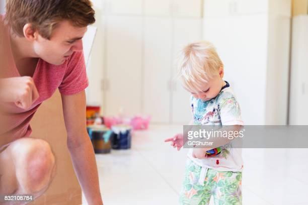 Vater Biegen bis zu spielen mit seinem Sohn und sein Spielzeug