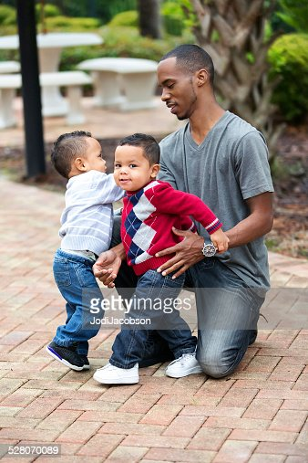 A father bending down with his two cute twin sons outdoors.