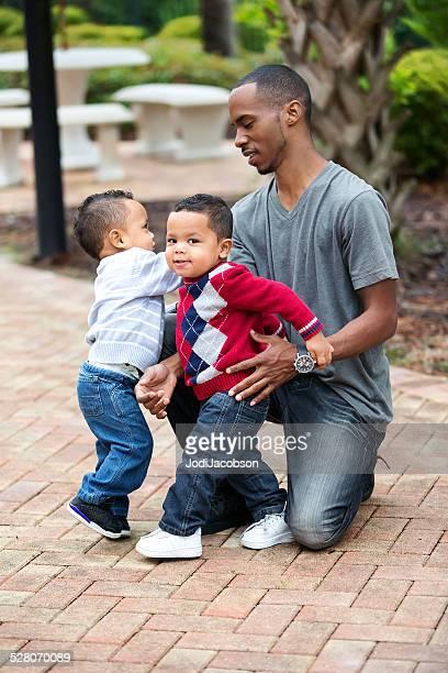 Ein schwarzer Vater mit seinen zwei Jahre alten Jungen mit zwei Einzelbetten