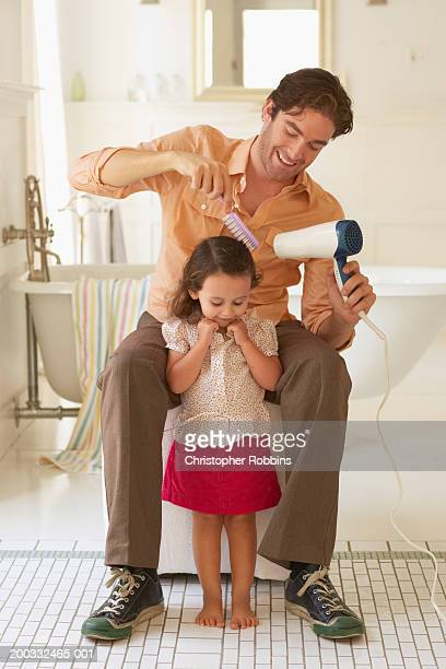Father blowdrying daughter's (2-4) hair in bathroom