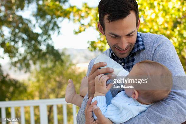 Father bottle feeding son outdoors