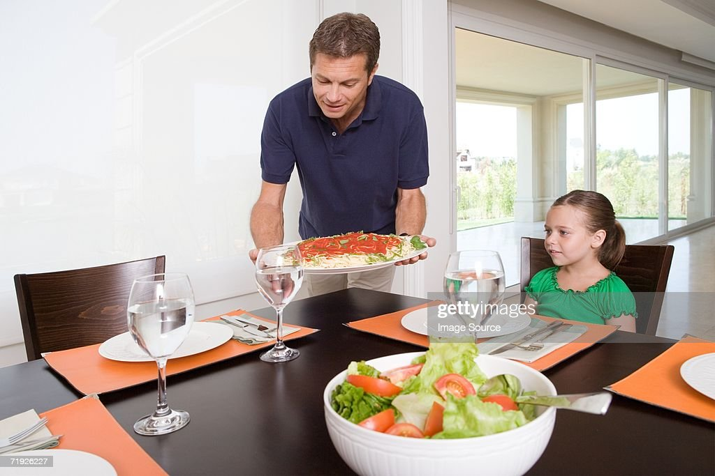 Father bringing meal to table : Stock Photo