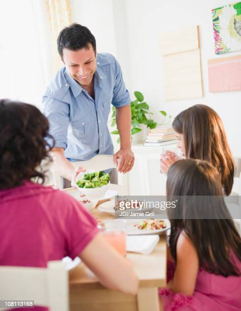 Father bringing salad to table for family dinner