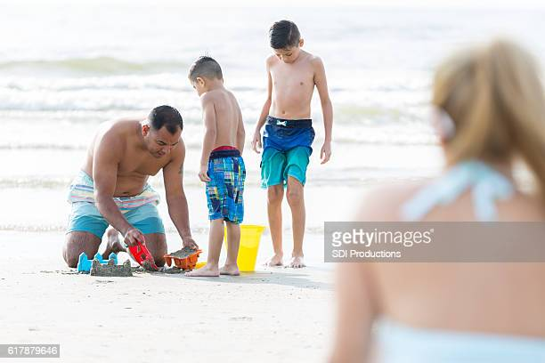 Father builds sandcastle with sons