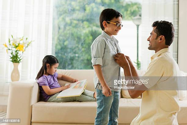 Father buttoning son's shirt while daughter (6-7) reading book on sofa
