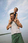 Father by sea with son (4-5 years) on  shoulders