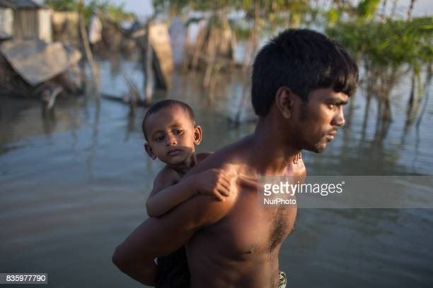 A father carries his child on his back Sariakndi outskirt of Bogra Bangladesh August 20 2017