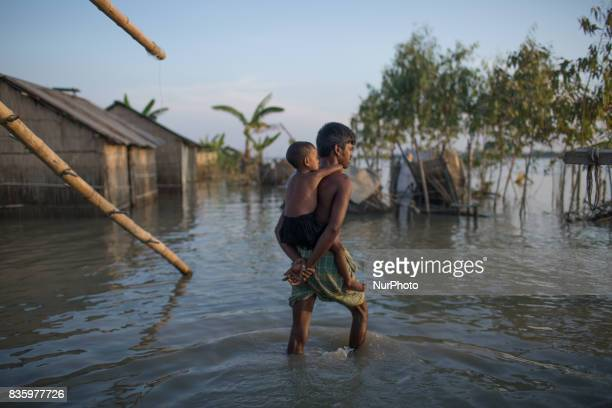 Father carries his daughter on the back and makes his way through flood water in Sariakndi outskirt of Bogra Bangladesh August 20 2017
