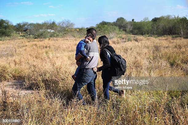 A father carries his sleeping son after their family illegally crossed the USMexico border on December 7 2015 near Rio Grande City Texas The father...