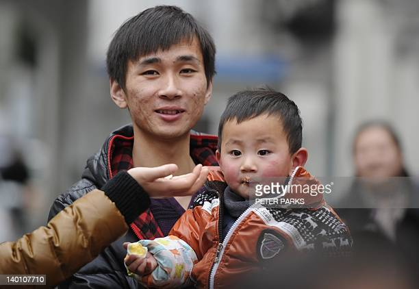 A father carries his son in Shanghai on February 28 2012 China is ordering local officials to stop using threatening slogans to enforce its strict...