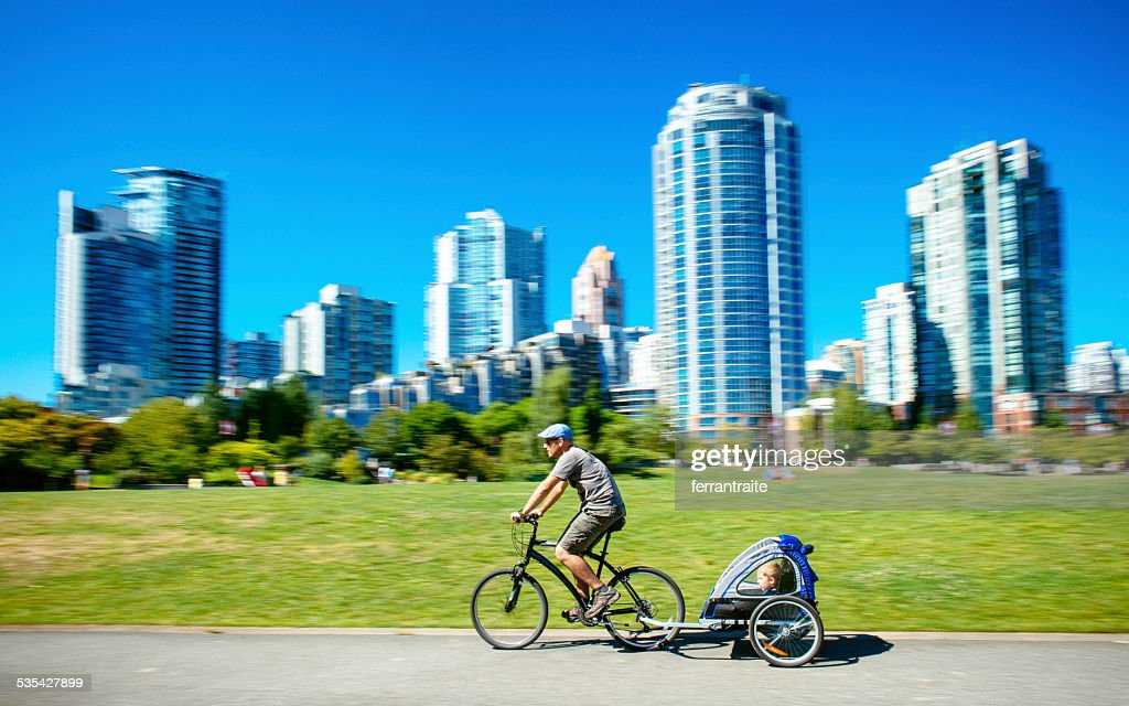 Father carries son in bicycle trailer in Vancouver Canada : Stock Photo