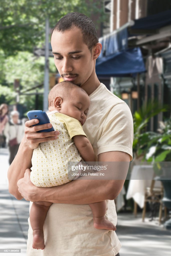 Father carrying baby and using cell phone