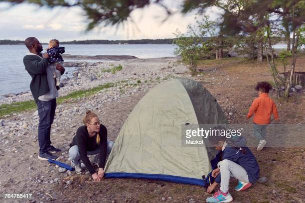 Father carrying baby boy while woman and daughter setting tent at beach