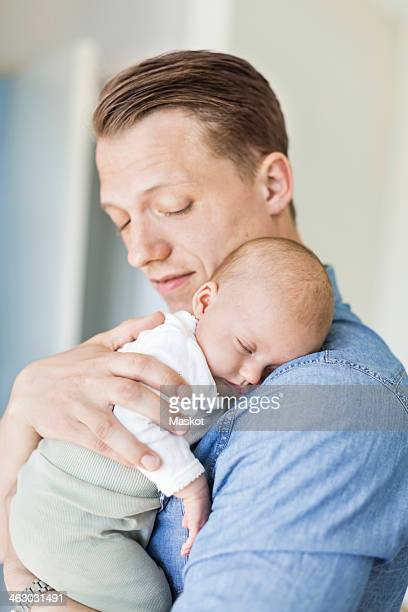 Father carrying baby girl at home