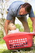 Father Carrying Baby Girl Sitting In Laundry Basket
