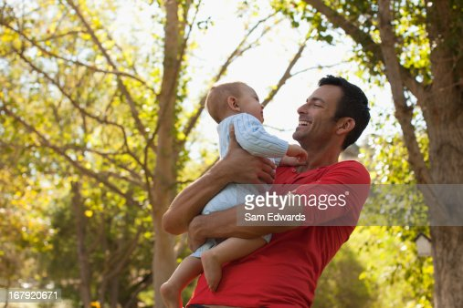 Father carrying baby outdoors : Stock Photo