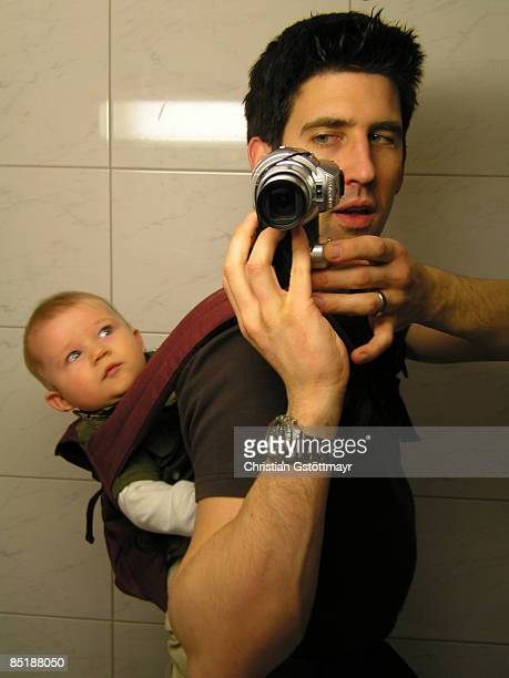 Father Carrying Baby While Photographing