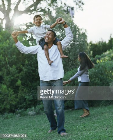 Father carrying boy (2-4) on shoulders in garden, smiling : Stock Photo