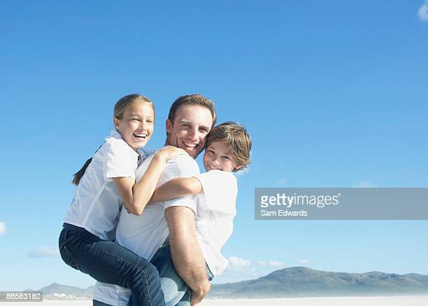 Father carrying children at beach