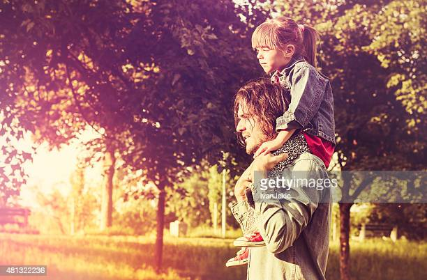 Father carrying daughter on his shoulders in nature at sunset