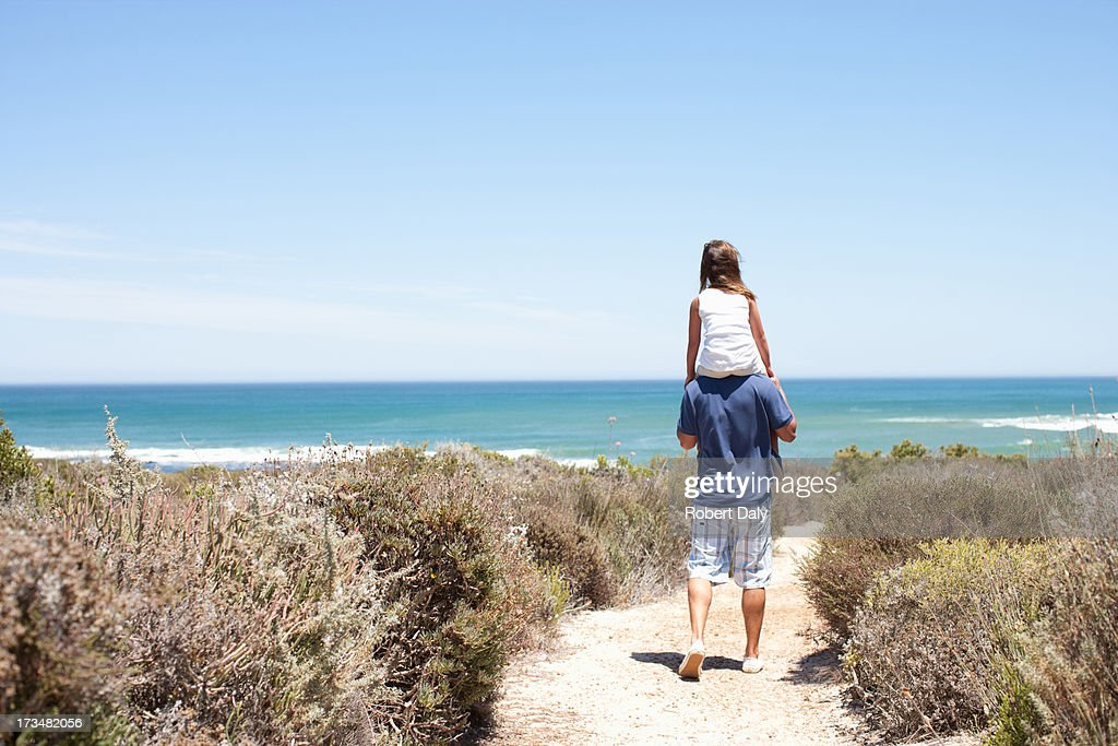 Father carrying daughter on shoulders on beach path : Stock Photo