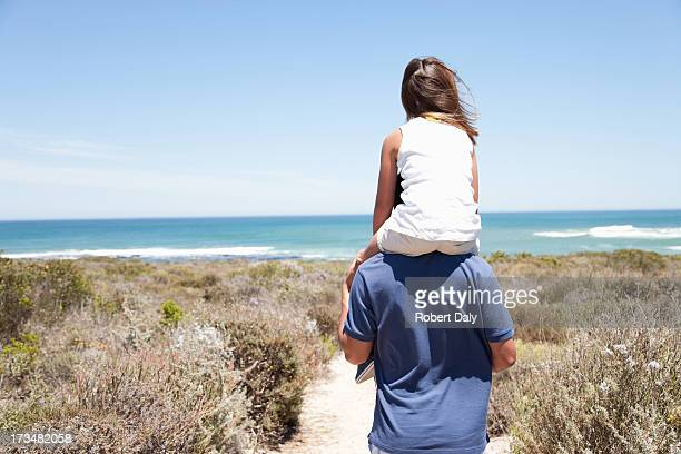 Father carrying daughter on shoulders on beach path