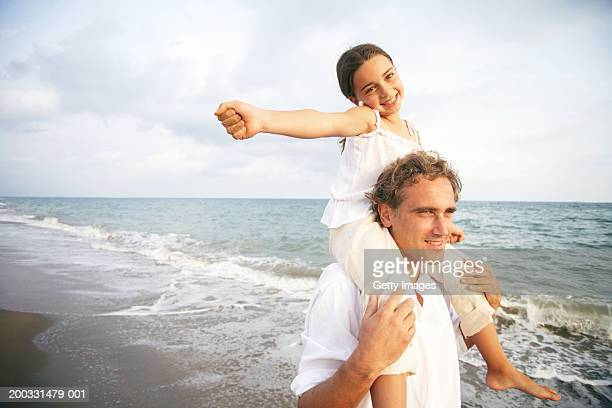 Father carrying daughter (6-8) on shoulders, on beach, portrait