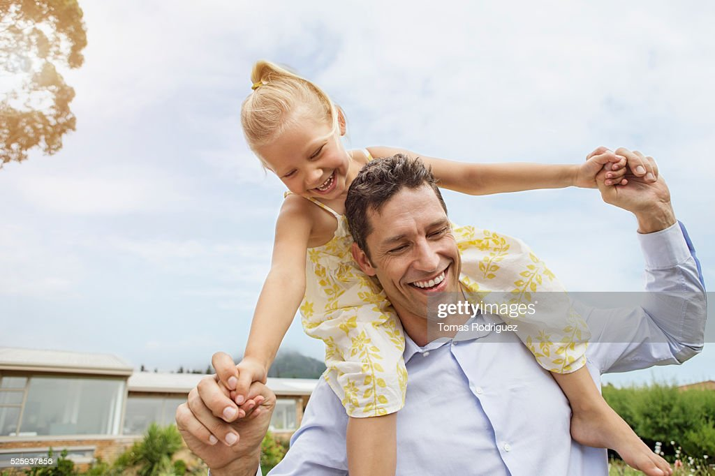 Father carrying daughter (4-5) on shoulders : Foto de stock