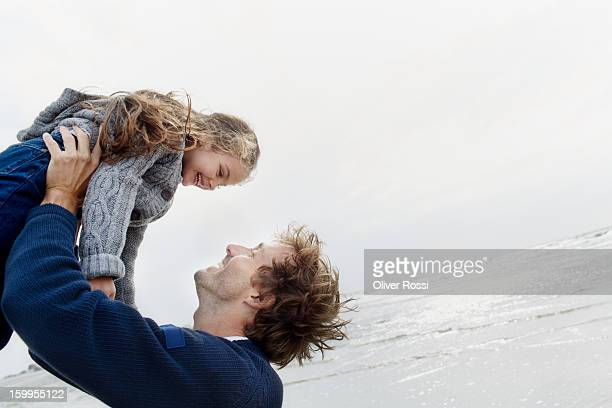 Father carrying daughter on the beach