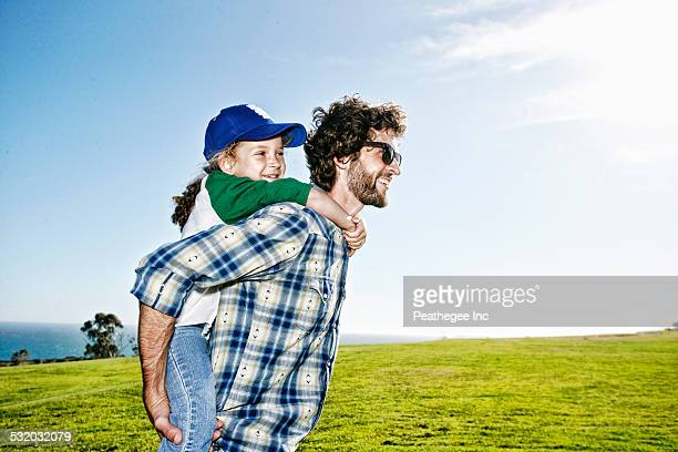 Father carrying daughter piggyback in grassy field
