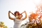 Father carrying daughter piggyback and being truly happy