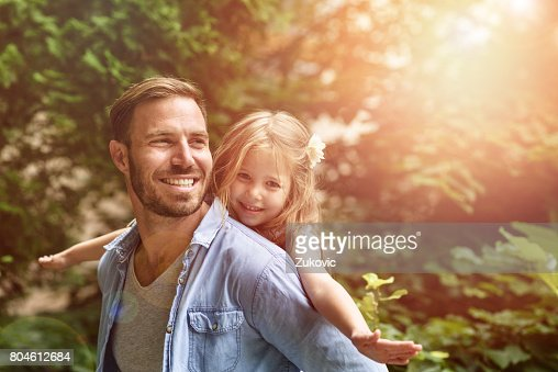 Father carrying daughter piggyback : Stock Photo