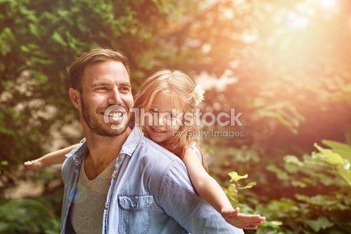 Father carrying daughter piggyback : Stock Photo