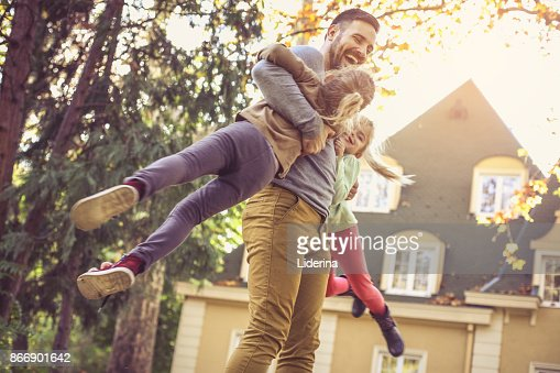 Father carrying daughters around neck.  Side view. : Foto de stock