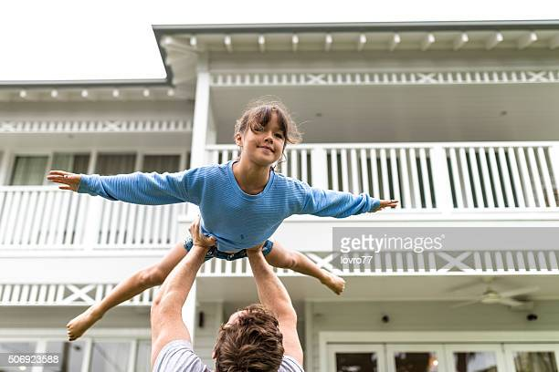 Father carrying his daughter on hips in front of house