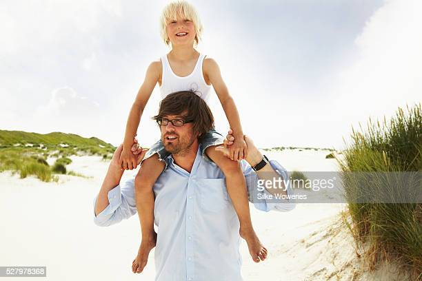 father carrying his little son pickaback on a beach