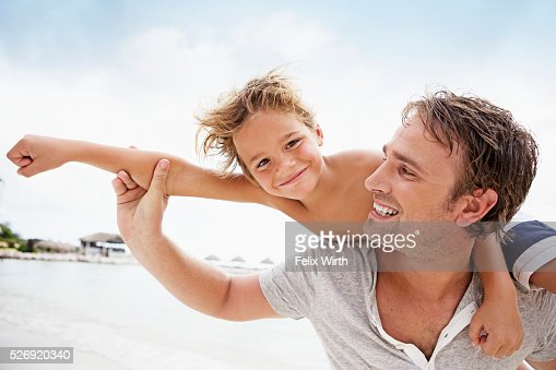 Father carrying his son (4-5) on shoulder : Foto de stock