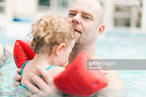 Father carrying little daughter in swimming pool