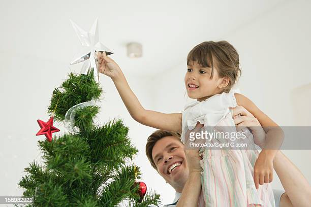 Father carrying little girl putting star on tip of Christmas tree
