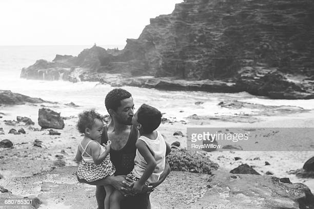 Father carrying son and daughter, kissing son on beach
