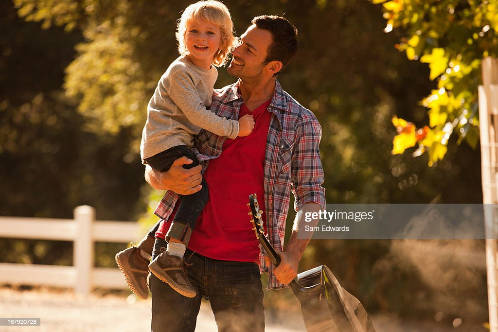 Father carrying son and guitar outdoors : Stock Photo