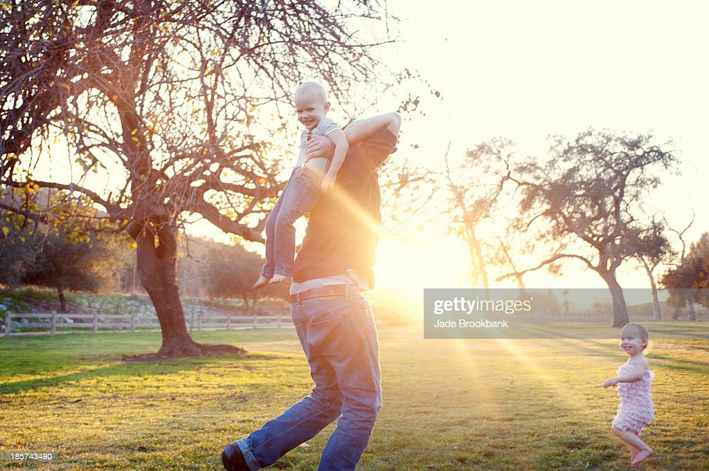 Father carrying son in sunlit field