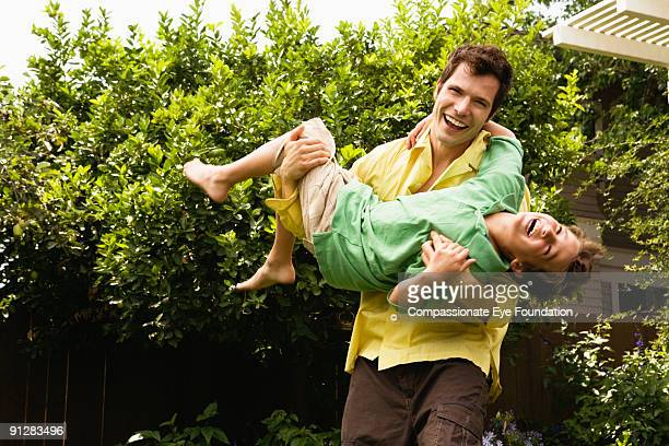 Father carrying son, laughing
